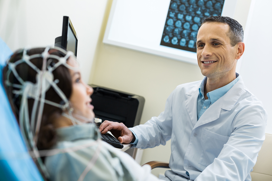 Precise data. The focus being on a charming pleasant medical specialist recording electroencephalographic waves of the brain of a beautiful young woman