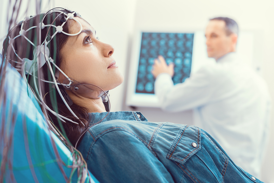 Close up of young woman getting brain analyzed by electroencephalograph